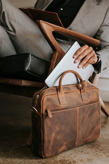 Empresário elegante colocando seu laptop em sua bolsa de couro marrom