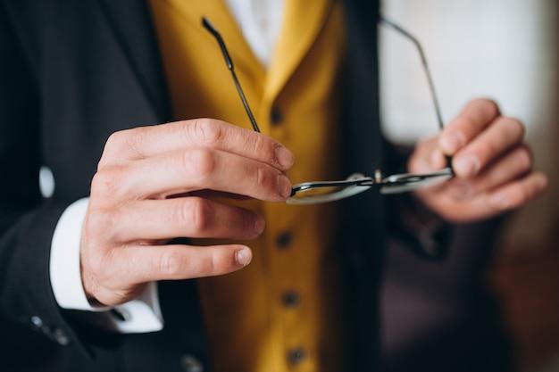 Empresário elegante de terno clássico, colocar óculos de sol