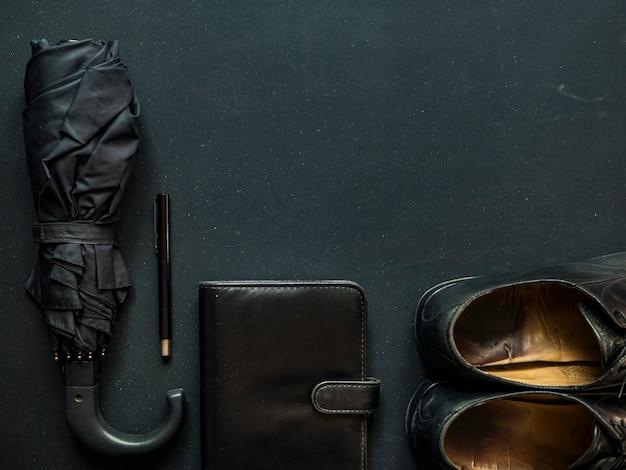 Empresário elegante na moda masculina fornece guarda-chuva sapatos caderno e caneta cópia espaço
