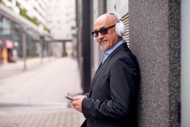 Empresário elegante profissional maduro está ouvindo música no telefone com fones de ouvido enquanto inclinando-se contra a parede na rua.