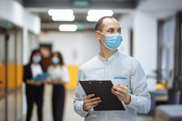 Empresário elegante usando uma máscara médica fica no corredor do escritório com um tablet nas mãos.