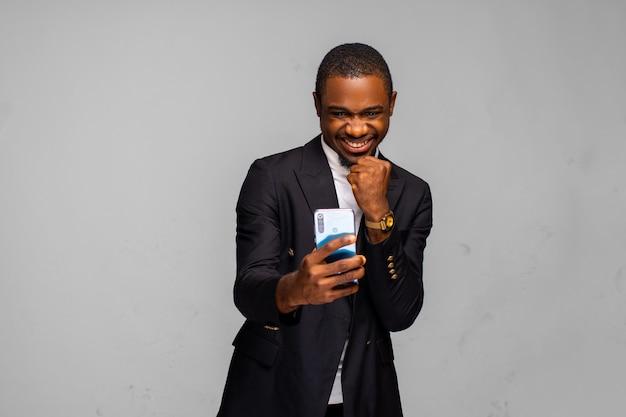 Empresário em êxtase aprendendo boas notícias no smartphone