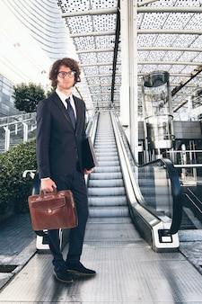 Empresário em frente a uma escada rolante em um escritório moderno