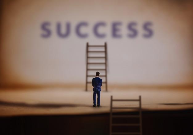 Empresário em miniatura com escada de sucesso da escada