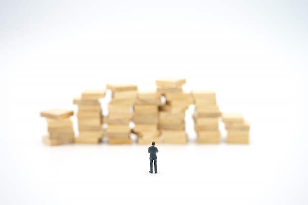 Empresário em miniatura com pilha de notas de pé