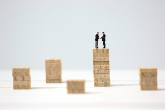Empresário em miniatura cooperar em pilhas de madeira mais altas.