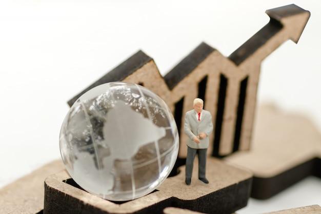 Empresário em miniatura em pé com globo e gráfico