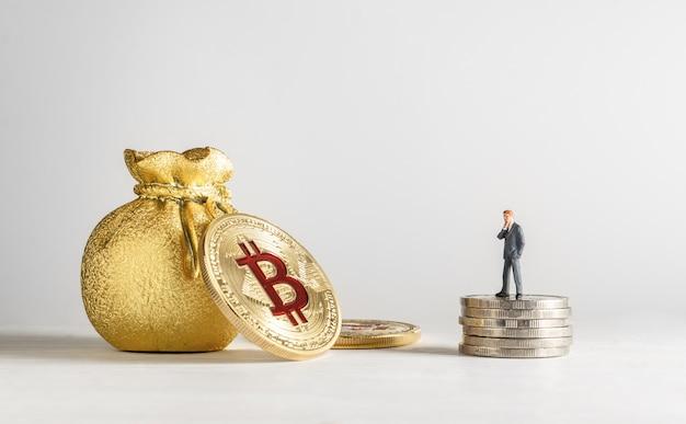Empresário em miniatura em pé sobre as moedas e olhando para bitcoin dourado