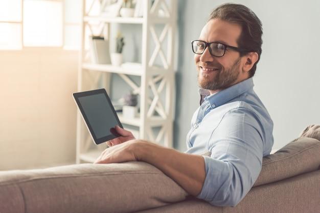 Empresário em óculos está usando um tablet digital.
