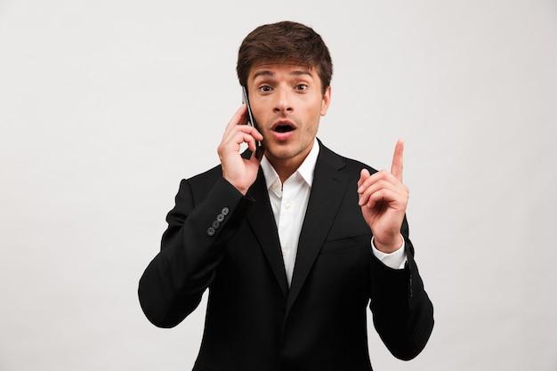 Empresário em pé isolado falando por apontar do telefone móvel.