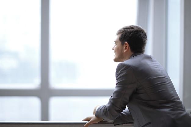Empresário em pé perto da janela e olhando para ela.