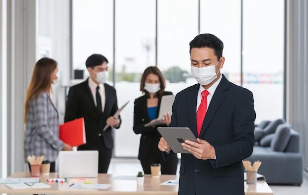 Empresário em pé segurando o celular no escritório