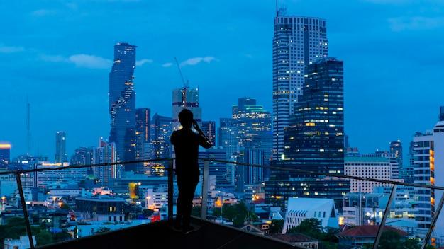 Empresário em pé usando telefone inteligente na varanda superior do telhado aberto, assistindo a visão noturna da cidade. negócios com ambição e visão.