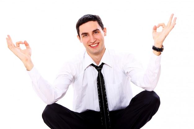 Empresário em pose de ioga, mostrando sinal de ok