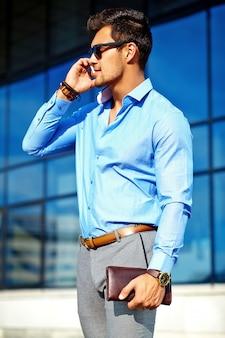 Empresário em roupa formal e óculos de sol, usando seu telefone