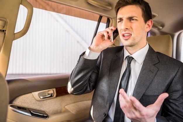 Empresário em seu carro de luxo e falando ao telefone.