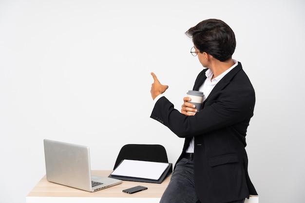 Empresário em seu escritório, apontando para trás com o dedo indicador