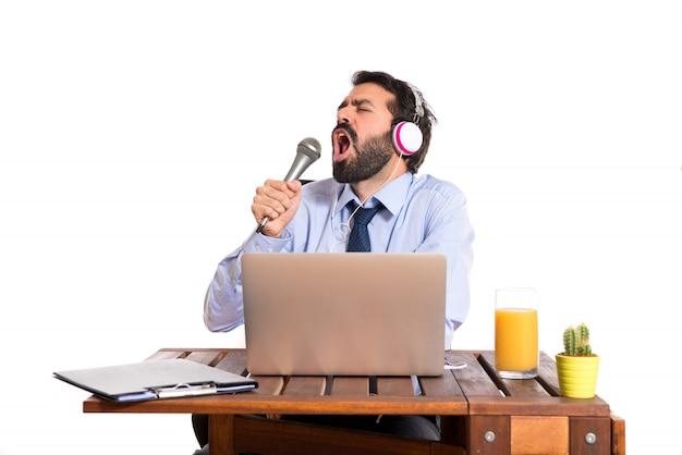 Empresário em seu escritório cantando