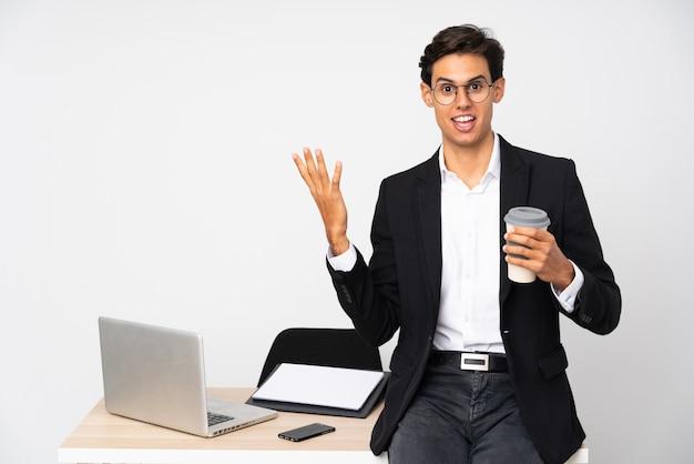 Empresário em seu escritório com expressão facial de surpresa