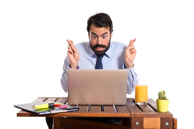 Empresário em seu escritório com os dedos cruzados