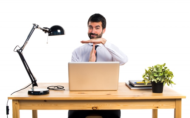Empresário em seu escritório fazendo um gesto de tempo limite