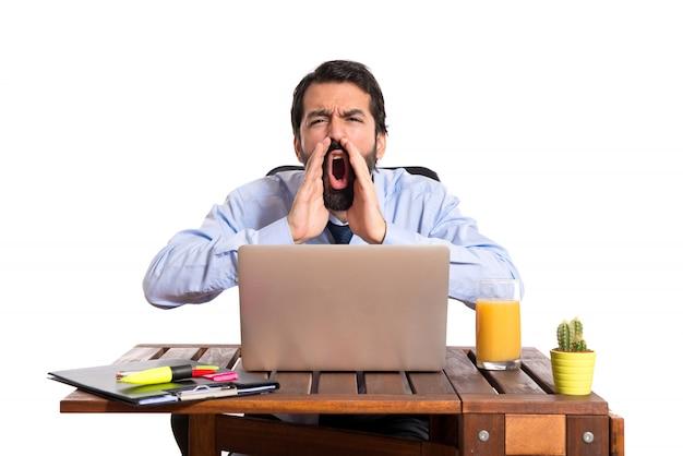 Empresário em seu escritório gritando
