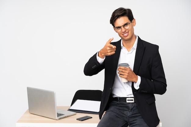 Empresário em seu escritório sobre parede branca aponta o dedo para você