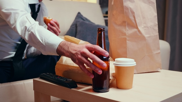 Empresário em sua casa descansando e bebendo cerveja. alimentos não saudáveis