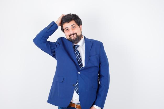 Empresário em terno formal, colocando a mão na cabeça e olhando feliz, vista frontal.