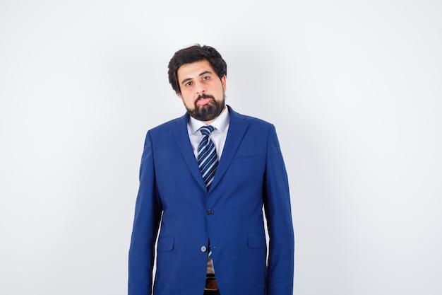 Empresário em terno formal de pé em linha reta e posando e olhando sério, vista frontal.