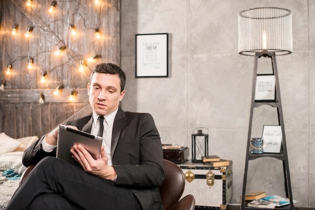 Empresário em terno navegando tablet