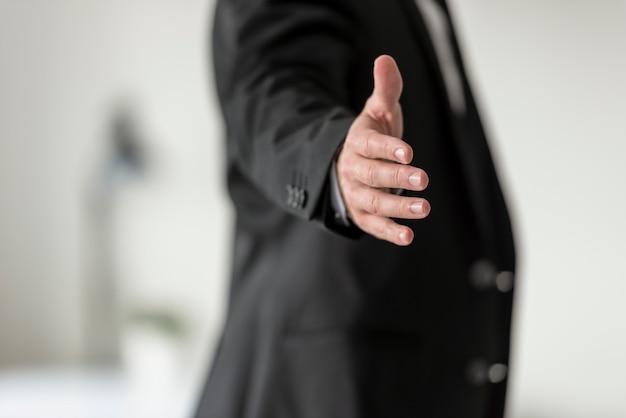 Empresário em terno preto, oferecendo-lhe um aperto de mão