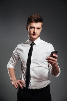 Empresário em trajes formais, segurando o telefone móvel