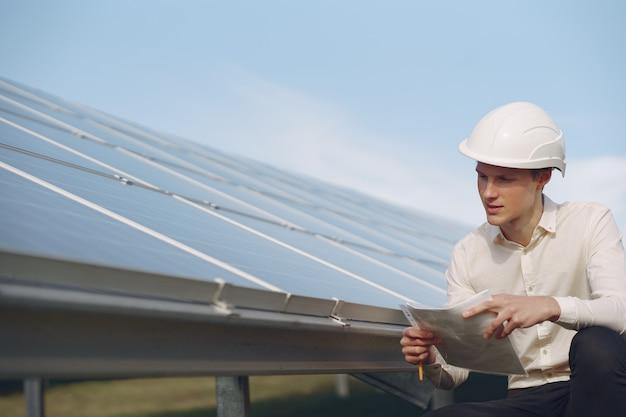 Empresário em um capacete branco perto da bateria solar