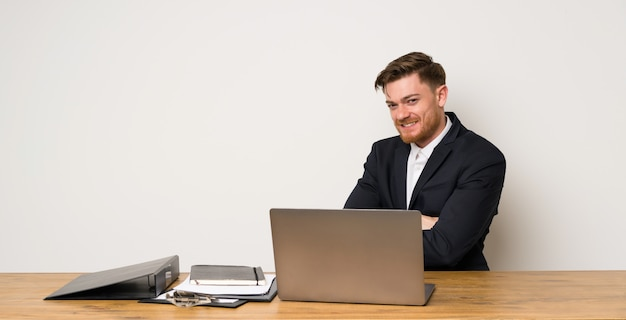 Empresário em um escritório com os braços cruzados e olhando para a frente
