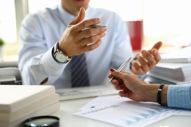 Empresário em um escritório tem caneta na mão e discute um plano de negócios para 2021 com o colega.