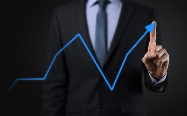 Empresário em um fundo preto pressiona, pressiona um dedo em um arro de crescimento positivo