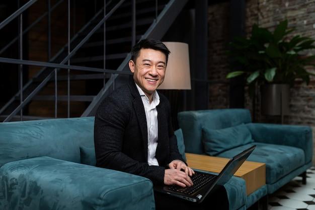Empresário em um terno preto trabalha em um laptop
