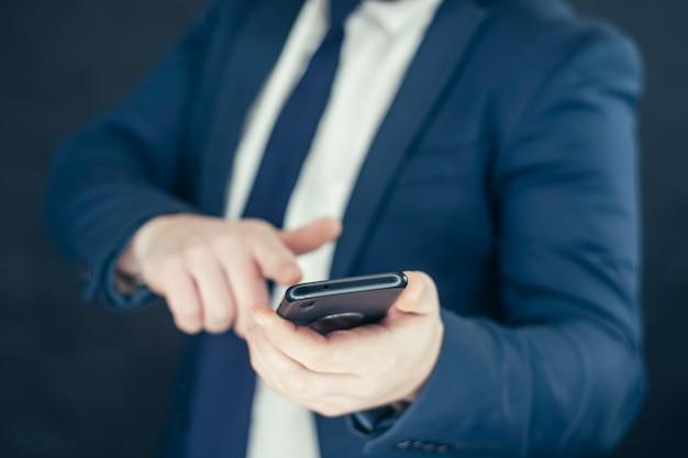 Empresário em uma camisa e um casaco azul com smartphone na mão.