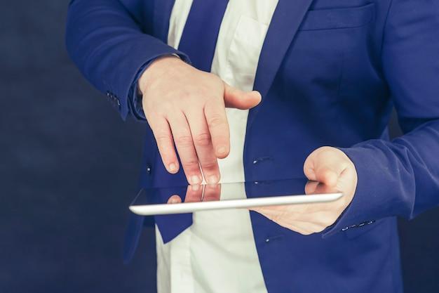Empresário em uma camisa e uma jaqueta azul com o tablet na mão.