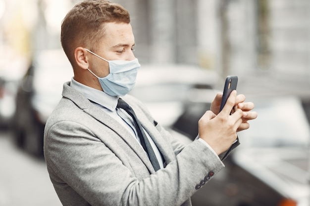 Empresário em uma cidade. pessoa com máscara. cara com telefone.