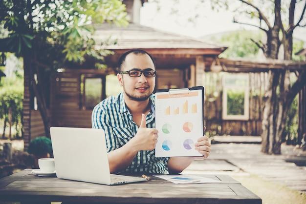 Empresário em uma reunião ou apresentação, apontando com documento de gráfico comercial na mesa.