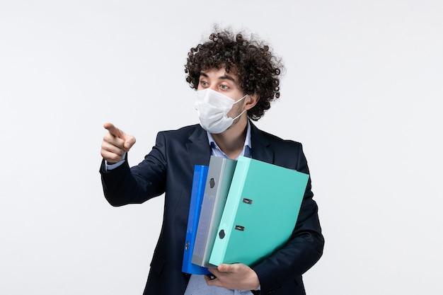 Empresário emocional de terno e máscara segurando documentos apontando para a frente na superfície branca