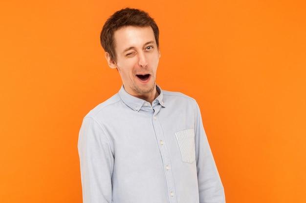 Empresário emocional vestindo camisa azul piscando para a câmera