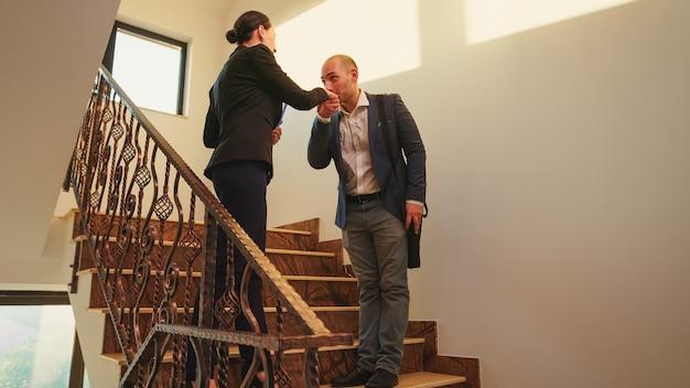 Empresário, encontrando-se nas escadas em uma empresa corporativa de finanças com o gerente executivo, apertando as mãos. equipe de empresários profissionais trabalhando em um edifício financeiro moderno, cumprimentando e conversando com cada um