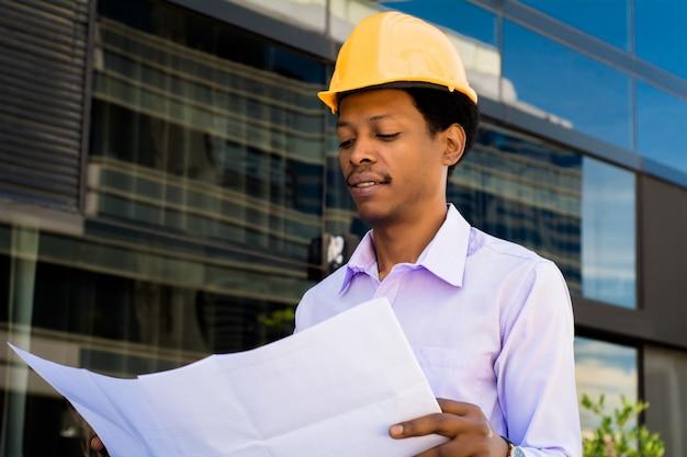 Empresário engenheiro desenvolvedor segurando blueprint