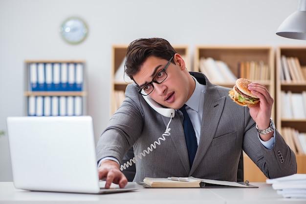 Empresário engraçado com fome comendo sanduíche de junk food