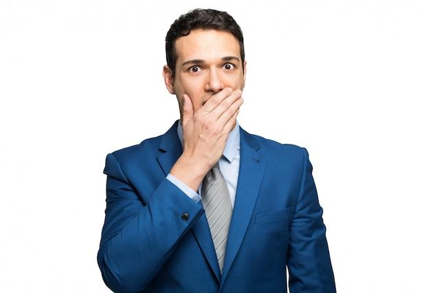 Empresário engraçado está cobrindo a boca com as mãos. isolado no fundo branco.