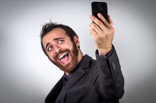 Empresário engraçado está usando seu smartphone para tirar uma selfie