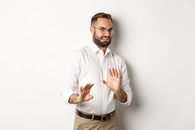 Empresário enojado rejeitando algo ruim, encolhendo-se de aversão, mostrando uma placa de pare